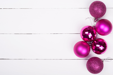 pink christmas: Christmas background. Pink Christmas ornaments on a white wooden background. Lot of copyspace
