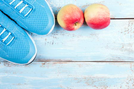 Sport shoes and apples on wooden background. Top view sport equipment. Healthy life concept