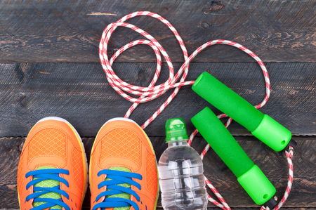 Sport shoes, skipping rope and bottle of water on the old wooden background. Sports equipment. Sport and healthy life concept. Top view
