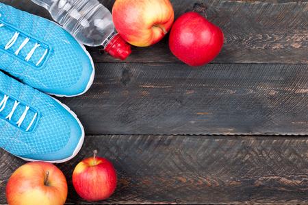 Calzado deportivo, manzanas y una botella de agua sobre fondo de madera oscuro. Equipo de deporte. Fondo de concepto de vida saludable activa. Vista superior Foto de archivo