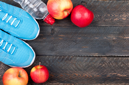 Sport shoes, apples and bottle of water on dark wooden background. Sport equipment. Active healthy life concept background. Top view