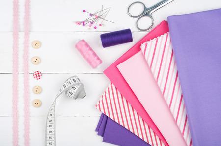 coser: Fondo de costura. Tejidos de algodón, carretes de hilo, tijeras, botones, cinta métrica, equipos de coser. Accesorios para coser en el fondo de madera blanca. Ajuste de la vista superior de la costura