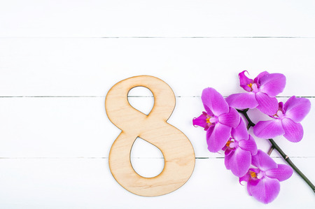 8 March International Womens Day background with copy space. 8 march greeting card with blooming orchid flowers on white wooden table. Rustic style