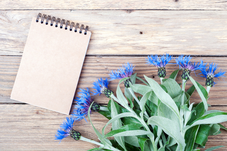 garden cornflowers: Bouquet of cornflowers and open notebook on old wooden background with copy space. Summer flowers. Holiday card. Top view