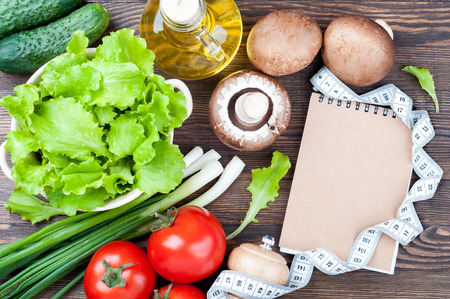 Fresh organic vegetables. Lettuce, cucumber, tomatoes, green onions, mushrooms champignons, olive oil, open notebook and measuring tape on wooden background. Healthy food, diet and cooking concept. Copy space. Top view