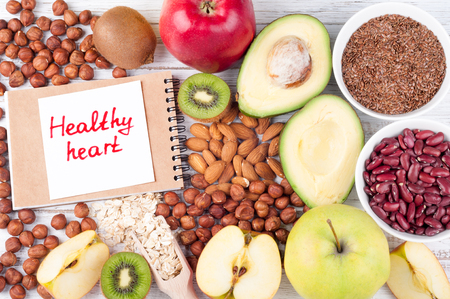 Healthy food that is useful for the heart on wooden background with note Healthy heart. Diet and healthy lifestyle concept. Top view