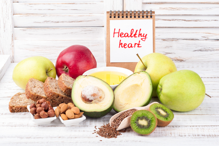 Healthy fat sources and healthy food that is useful for the heart on wooden background with note Healthy heart. Diet and healthy lifestyle concept. Copy space