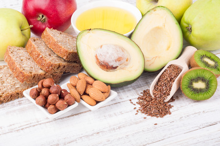 Healthy fats sources and healthy food - avokado, flax seeds, olive oil, whole grain bread, nuts, kiwi and apples on wooden background with copy space. Diet and healthy lifestyle concept. Vegetarian food. Top view Stock Photo