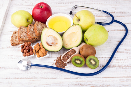 Healthy fats and healthy food that is good for heart, stethoscope on wooden background. Diet and healthy lifestyle concept