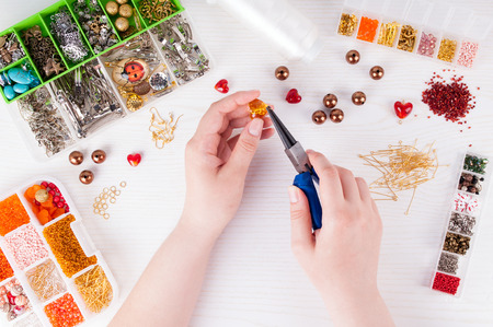 jobbing: Woman making handmade jewellery. Boxes with beads, glass hearts, accessories for needlework on white wooden table. Handmade accessories. Top view Stock Photo