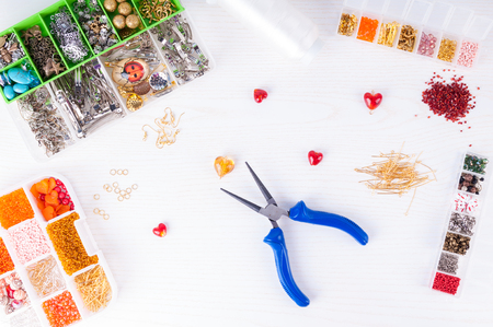 bead embroidery: Process of  making handmade jewelry. Boxes with beads, pliers, threads, equipment and accessories for handmade on wooden table. Top view. Top view