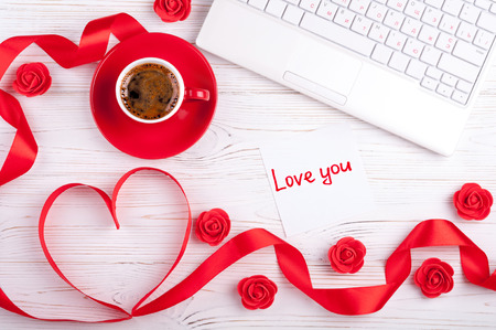 Valentines background with red heart, coffee cup, laptop and roses. Valentines Day greeting card. Female workplace. Top view Stock Photo