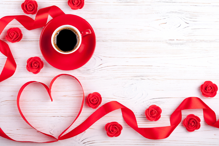 Valentines background with red heart, coffee cup and roses. Valentines Day greeting card. Top view