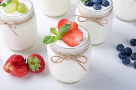 Fresh yogurt with berries in glass jars. Healthy food, dieting and breakfast concept. Close up