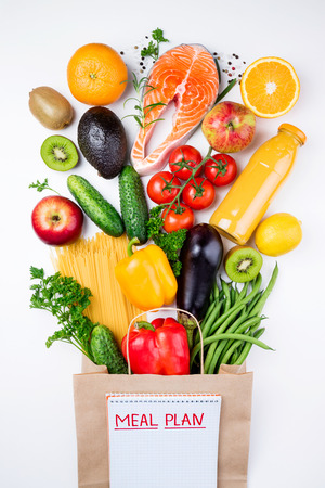 Healthy food background. Healthy food in paper bag fish, vegetables and fruits on white. Shopping food concept. Top view Standard-Bild