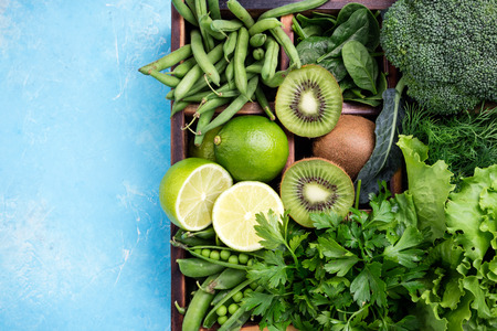 Green vegetables background. Fresh garden produce. Broccoli, spinach, kiwi, lettuce, parsley, dill, asparagus beans on blue concrete background, top view and copy space Stock Photo