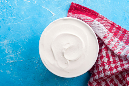 Yogurt on blue background. Dairy product. Healthy food and diet concept. Copy space. Top view