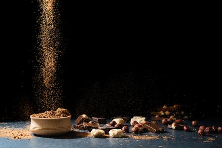 Kakaopulver in Bewegung. Schokoladenstaub, Kakaoprodukte, Nüsse auf schwarzem Hintergrund. Platz kopieren