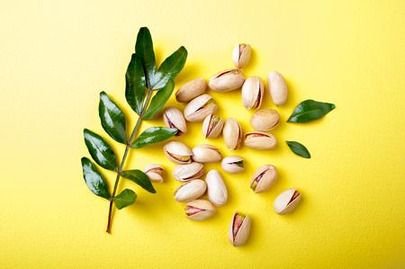 Pistazien mit Blättern auf gelbem Hintergrund, Ansicht von oben. Satz Pistazien. Flach legen
