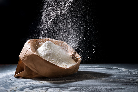 Bag with flour and sifting flour on black background. Cooking, baking, cooking bread concept