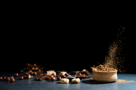 Cocoa powder in motion. Chocolate dust, cacao products, nuts on black background. Copy space