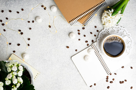 Cup with coffee and home decor on white background. Coffee, flowers, notebooks and led lights, cozy weekend concept, top view. Copy space