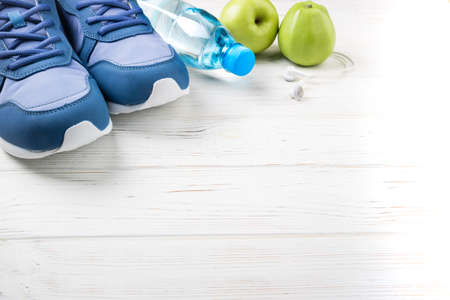 Sport shoes, bottle of water, apples and earphones on white wooden background. Sport equipment. Healthy lifestyle, sport and diet concept. Long web format. Copy space