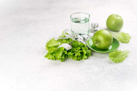 Healthy food. Green apple, lettuce salad, glass of water, measuring tape on white background. Dieting, slimming, healthy eating concept. Copy space