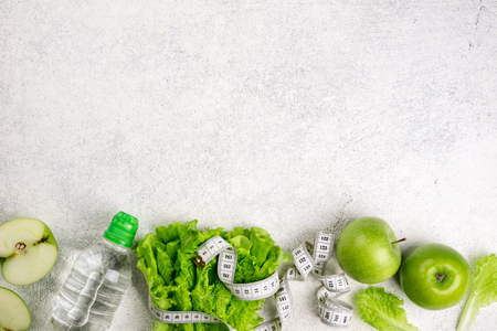 Healthy food. Green apple, lettuce salad, bottle of water, measuring tape on white background. Dieting, slimming, healthy eating concept. Copy space, top view