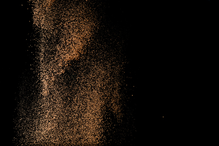 Cocoa powder sifting isolated on black background. Chocolate dust on black background. Copy space