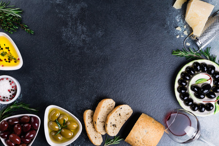 Olives, red wine, ciabatta bread, cheese, oil, herbs and spices on black stone background. Mediterranean snacks. Appetizer gourman food. Copy space, top view