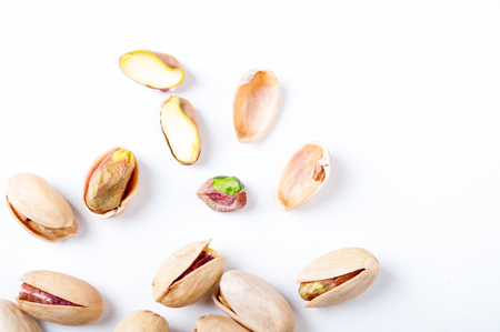 Pistachios nuts on white background, top view. Flat lay