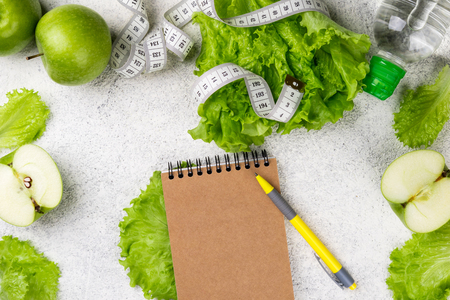 Healthy eating. Green apple, lettuce salad, water bottle, measuring tape. Dieting, slimming, weight loss and meal planning concept. Copy space and top view Stock Photo