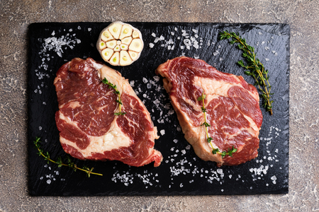Raw meat with herbs and spices. Raw beef steak on cutting board with thyme and garlic for cooking. Top view Stock Photo