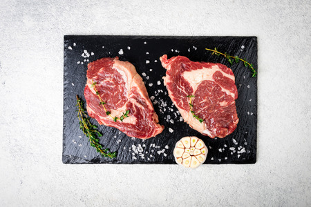 Raw meat. Raw beef steak on a cutting board with rosemary and spices, top view. Cooking meat Stock Photo