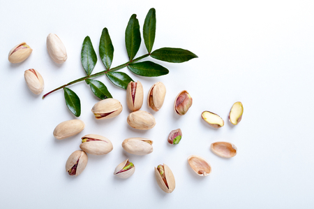 Pistachios with leaves on white background, top view. Set of pistachio nuts. Flat lay Stock Photo