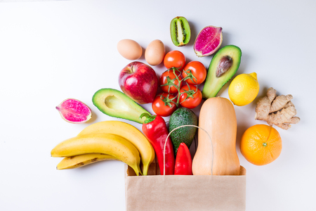 Healthy food background. Healthy food in paper bag fruits and vegetables on white. Vegetarian food. Shopping food supermarket concept. Top view Stock Photo