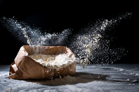 Bag with flour and egg flying in flour on black background. Flour splash. Cooking, baking concept