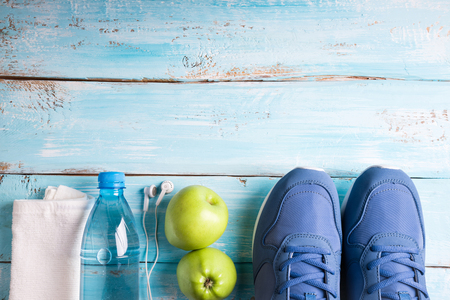 Flat lay sport shoes, bottle of water, apples, towel and earphones on white background. Sport equipment. Healthy lifestyle, sport and diet concept. Copy space, top view