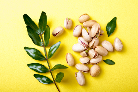 Pistachios with leaves on yellow background, top view. Set of pistachio nuts. Flat lay