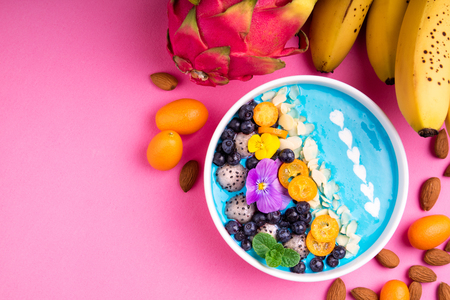 Smoothie bowl with fruits, berries, nuts and flowers. Tropical healthy smoothie dessert. Healthy breakfast, vegetarian, dieting concept. Top view, flat lay Stock Photo