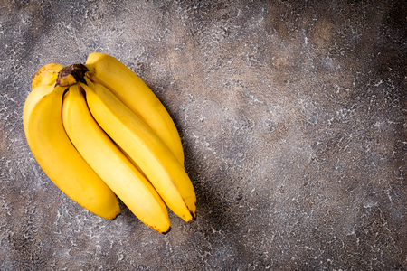 Bananas on concrete background. Fresh yellow banana on dark stone table. Top view, copy space