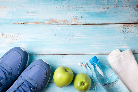 Flat lay sport shoes, bottle of water, apples, towel and earphones on blue wooden background. Healthy lifestyle, sport and diet concept. Top view, copy space