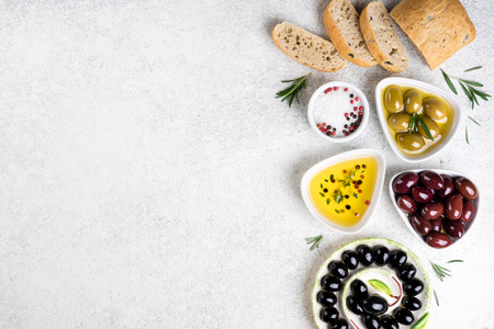 Ciabatta bread, olives, cheese, oil, herbs and spices on white background. Mediterranean snacks. Copy space, top view