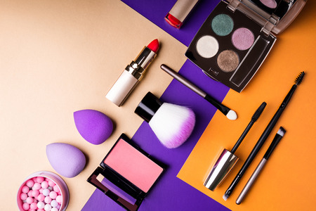 Makeup products and decorative cosmetics on color background flat lay. Fashion and beauty blogging concept. Top view, copy space Stock Photo