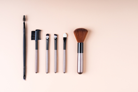 Cosmetics accessories for makeup on beige background flat lay. Set of cosmetics brushes. Minimal composition. Fashion and beauty blogging concept. Top view, copy space