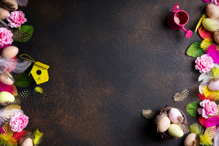 Easter background. Easter composition: eggs, nest with eggs, flowers, feathers and easter decorations on aged stone background. Top view, copy space