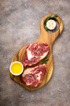 Raw meat. Raw beef steak on a cutting board with rosemary and spices, top view