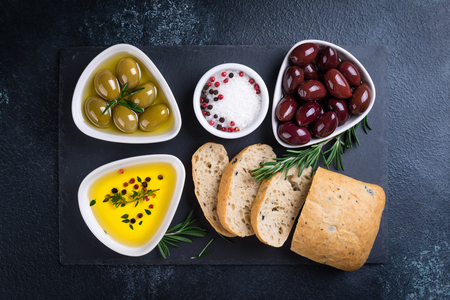 Olives, ciabatta bread, oil, herbs and spices on black stone slate background. Mediterranean snacks. Top view