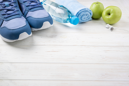 Flat lay sport shoes, bottle of water, apples, towel and earphones on white wooden background. Sport equipment. Healthy lifestyle, sport and diet concept. Copy space Stock Photo
